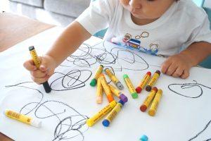 Kind malt mit Kreidestiften auf weisses Blatt