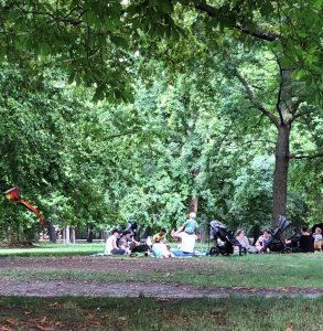 Menschengruppe mit Kindern sitzt auf Wiese im Wiener Prater