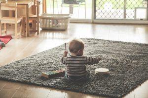 Baby sitzt auf Teppich im Zimmer und trommelt